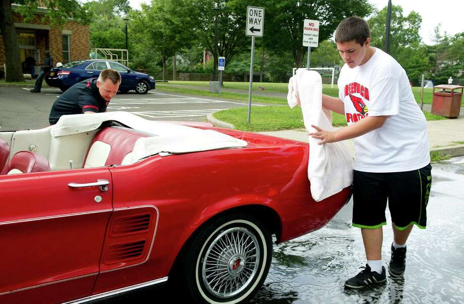 Greenwich High School football team member Joe Carriero, 14, helps wash cars to raise money for the team's booster club at Old Greenwich School on Saturday, August 23, 2014. Photo: Lindsay Perry / Stamford Advocate