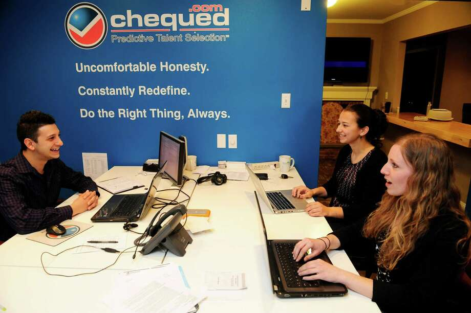 Andrew D'Agostino, left, Chequed.com product manager and senior consultant to the UAlbany science team, works with UAlbany doctoral students and interns, Lindsay Ciancetta, foreground, and Laura Santiago at Chequed.com offices on Monday, April 7, 2014, in Saratoga Springs, N.Y.  (Paul Buckowski / Times Union) Photo: Paul Buckowski / 00026382A