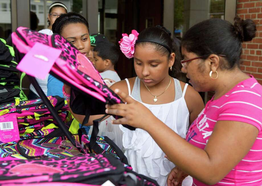 Briana Santiago, 9, and Veronica Jimenez, 17, choose backpacks during the Stamford Police Department's annual backpack giveaway at  Police Headquarters in Stamford, Conn., on Saturday, August 23, 2014. Photo: Lindsay Perry / Stamford Advocate