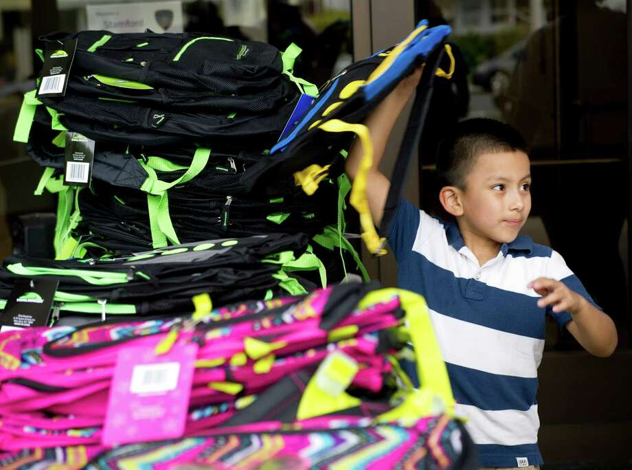Children choose backpacks during the Stamford Police Department's annual backpack giveaway at  Police Headquarters in Stamford, Conn., on Saturday, August 23, 2014. Photo: Lindsay Perry / Stamford Advocate