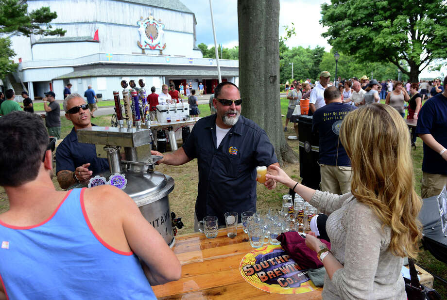 Southport Brewing Company's Master Brewer Mark daSilva hands a sample of their beer to Katie Foran, of Stratford, during the Shakesbeer Festival on the grounds of the American Shakespeare Festival Theater in Stratford, Conn. on Saturday August 23, 2014. The festival showcases fine craft beers from around Connecticut as well as nearby states. Photo: Christian Abraham / Connecticut Post