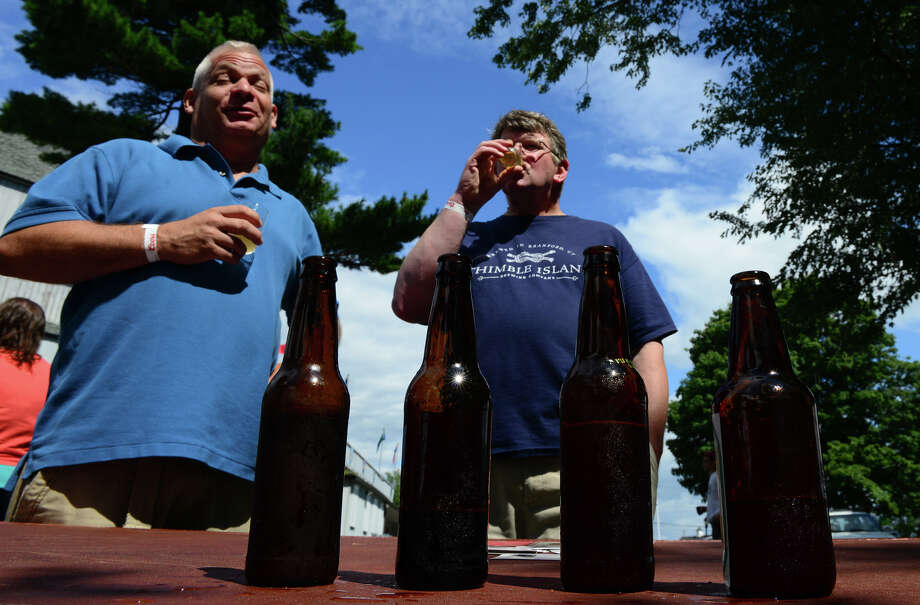 Andrew Parfitt, of North Branford, center, samples some beer from Blind Pug Ales, from Terryville, Conn, during the Shakesbeer Festival on the grounds of the American Shakespeare Festival Theater in Stratford, Conn. on Saturday August 23, 2014. At left is Andrew's friend Duane Hahnel. The festival showcases fine craft beers from around Connecticut as well as nearby states. Photo: Christian Abraham / Connecticut Post