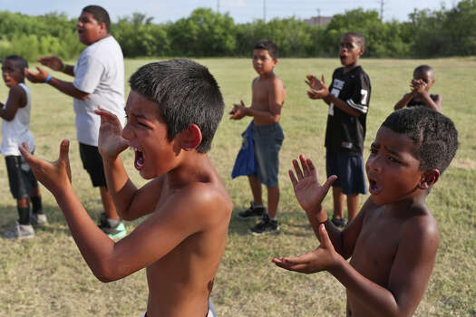 Juan Alvarez, 9, left, and Ellis Boston III, 5, cheer with the Texas Bad Boys football team as they run drills during practice at Woodard Park in San Antonio on Monday, August 4, 2014. Photo: Lisa Krantz / SAN ANTONIO EXPRESS-NEWS