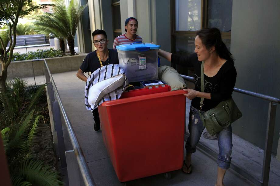 Austin Situ (left) carts his belongings into his dorm with help from brother Adrian Situ and mother J.C. Situ. Photo: Michael Short, The Chronicle