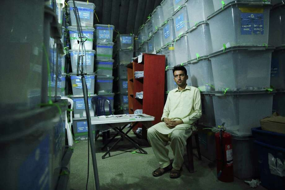 A worker for the Independent Election Commission is dwarfed by ballot boxes that were to be audited for evidence of fraud this month. More than 2 million ballots in the June 14 presidential runoff have been called into question. Photo: ANDREW QUILTY, STR / NYTNS