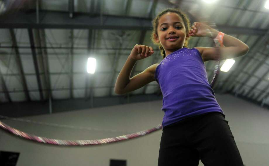 Sofia Allen, 6, of Bethel, hoola hoops during Kids Yoga Saturday, Aug. 23, 2014 at the Newtown Yoga Festival, to benefit the community fund of the Sandy Hook Promise Foundation. Photo: Autumn Driscoll / Connecticut Post