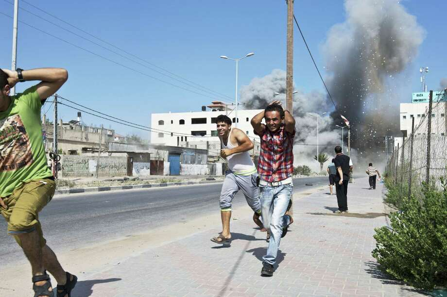 Palestinians run Saturday after a bomb from an Israeli airstrike brought down an apartment building in Gaza City after two warning missiles. Gaza officials said 11 children and five women were among 22 injured.  Photo: ROBERTO SCHMIDT, Staff / AFP