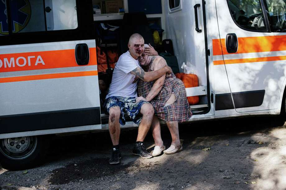 A wounded couple sit in an ambulance after shelling Saturday that killed three civilians in the main separatist stronghold of Donetsk, eastern Ukraine, where Kiev's army is fighting pro-Russian separatists. Photo: DIMITAR DILKOFF, Staff / AFP