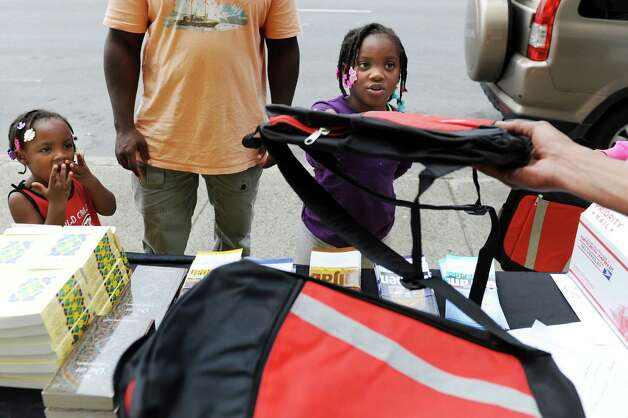 Hadiyah Hameed, 7, center, receives a free backpack filled with school supplies during the Back 2 School Giveaway project, a national effort by the Islamic Circle of North America, on Saturday, Aug. 23, 2014, at Masjid As-Salem Mosque in Albany, N.Y. At left is her sister Amirah Hameed, 3, who waits for her school bag. (Cindy Schultz / Times Union) Photo: Cindy Schultz / 00028245A