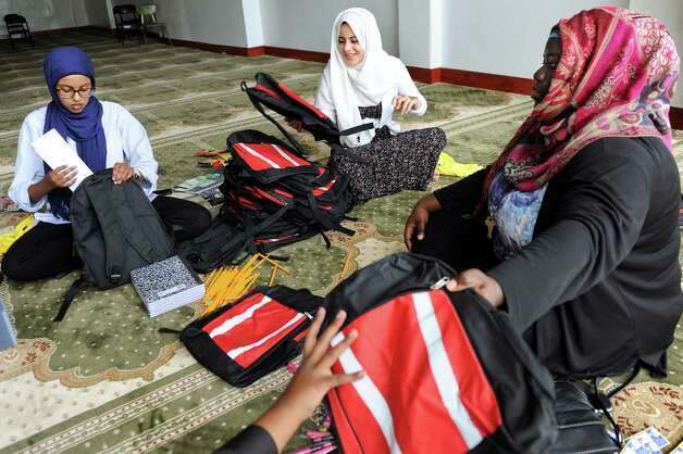 Mosque members Nasibah Elmi, 20, left, Alaa Muhiddin, 18, center, and Nurat Daniju, 20, form an assembly line as they fill backpacks with school supplies on Saturday, Aug. 23, 2014, at Masjid As-Salem Mosque in Albany, N.Y. (Cindy Schultz / Times Union) Photo: Cindy Schultz / 00028245A