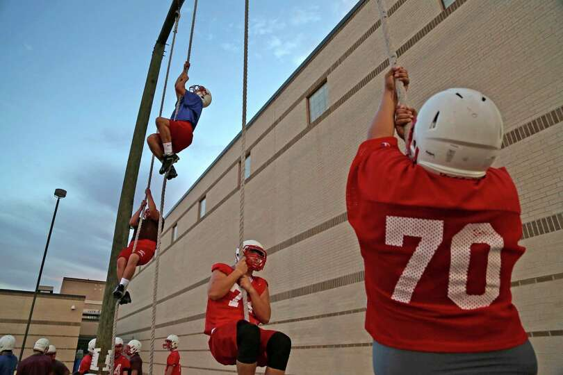 Katy High School football players climb ropes during conditioning at ...