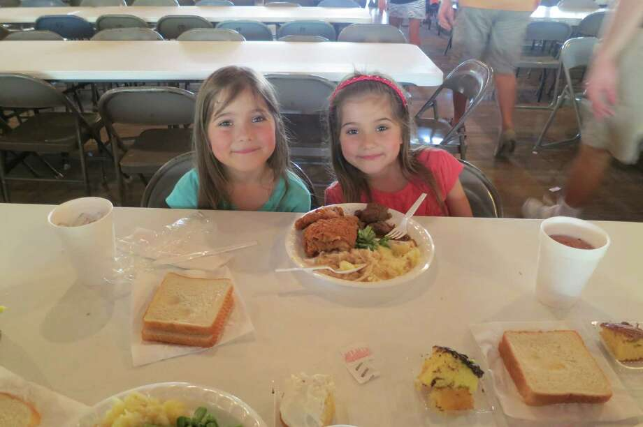 "Twins Julianna, left, and Olivia Jasek can't help smiling over the fried chicken and Praha stew they're about to share at the Praha Picnic. The 7-year-olds' father, Cliff Jasek of Bulverde, brought them to Praha to ""honor our heritage. Photo: Joe Holley / Houston Chronicle"