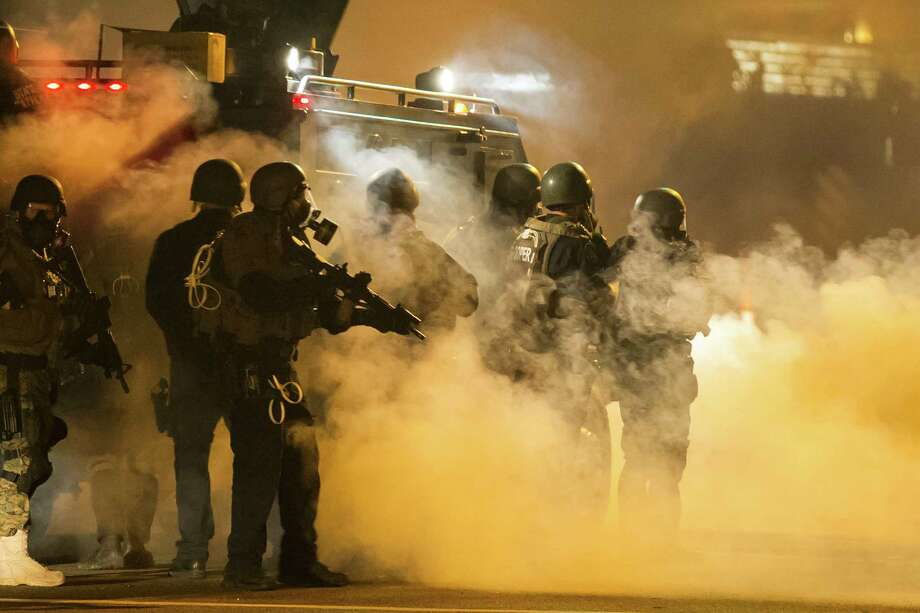 Heavily armed police fire tear gas last week in Ferguson, Mo. The spectacle of military-style weapons and vehicles used against civilians worries Washing- ton. Photo: WHITNEY CURTIS, STR / NYTNS