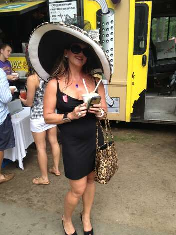 "Dr. Joy Lucas, a veterinarian from Saratoga Springs, has been coming to the Travers fashionably dressed for 17 years. She decrorated the hat herself. She was joined by ""a posse"" of friends in the Whitney booth, but made a long walk in 4-inch stiletto heels to buy a $7 cup of classic mac 'n cheese at the Mac Truck. (Paul Grondahl / Times Union)"
