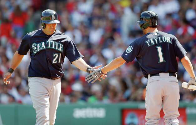 Seattle Mariners' Kendrys Morales (21) celebrates with Chris Taylor after scoring on a double by Chris Denorfia during the fourth inning of a baseball game against the Boston Red Sox in Boston, Saturday, Aug. 23, 2014. (AP Photo/Michael Dwyer) ORG XMIT: MAMD106 Photo: Michael Dwyer / AP