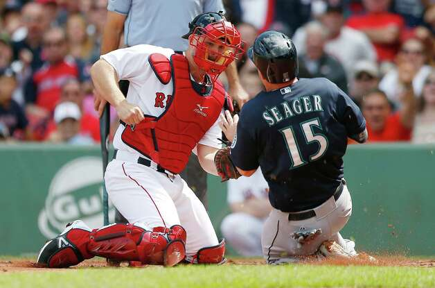 Boston Red Sox's David Ross, left, tags out Seattle Mariners' Kyle Seager (15) trying to score on a single by Jesus Sucre during the second inning of a baseball game in Boston, Saturday, Aug. 23, 2014. (AP Photo/Michael Dwyer) ORG XMIT: MAMD104 Photo: Michael Dwyer / AP