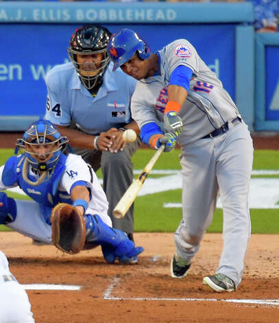 New York Mets' Juan Lagares, right, hits a three-run home run in front of Los Angeles Dodgers catcher Drew Butera and home plate umpire CB Bucknor during the fourth inning of a baseball game, Saturday, Aug. 23, 2014, in Los Angeles. (AP Photo/Mark J. Terrill)  ORG XMIT: LAD110 Photo: Mark J. Terrill / AP