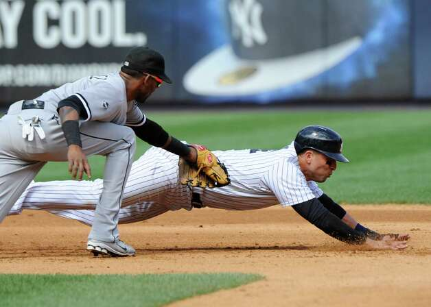 Chicago White Sox shortstop Alexei Ramirez, left,  tags out New York Yankees' Martin Prado on a fielder's choice during the fourth inning of a baseball game Saturday, Aug. 23, 2014, at Yankee Stadium in New York. (AP Photo/Bill Kostroun) ORG XMIT: NYY111 Photo: Bill Kostroun / FR51951 AP