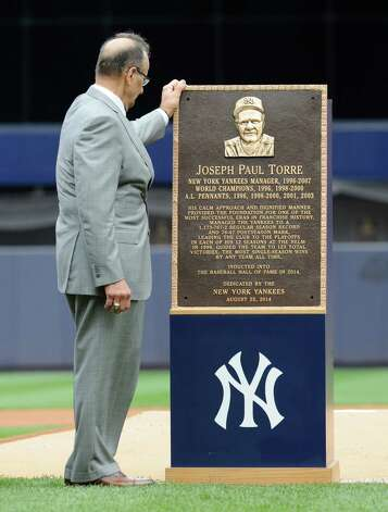 Former New York Yankees manager Joe Torre looks at a replica of his plaque that will hang in Monument Park as the Yankees retired his number before a baseball game against the Chicago White Sox Saturday, Aug. 23, 2014, at Yankee Stadium in New York. (AP Photo/Bill Kostroun) ORG XMIT: NYY101 Photo: Bill Kostroun / FR51951 AP