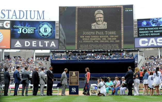 Former New York Yankees manager Joe Torre, center left, looks at a replica of his plaque that will hang in Monument Park as the Yankees retired his number before a baseball game against the Chicago White Sox Saturday, Aug. 23, 2014, at Yankee Stadium in New York. (AP Photo/Bill Kostroun) ORG XMIT: NYY103 Photo: Bill Kostroun / FR51951 AP