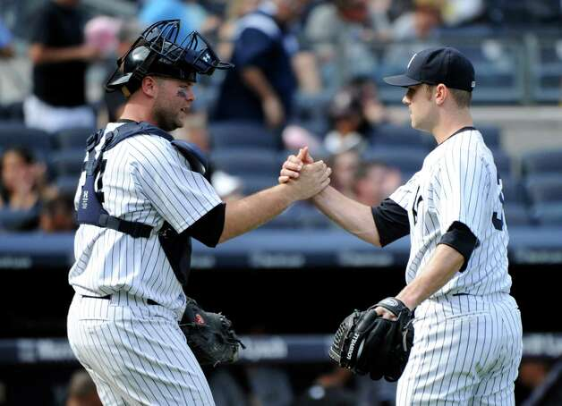 New York Yankees pitcher David Robertson, right, celebrates with catcher Brian McCann after the Yankees defeated the Chicago White Sox 5-3 in of a baseball game Saturday, Aug. 23, 2014, at Yankee Stadium in New York. (AP Photo/Bill Kostroun) ORG XMIT: NYY118 Photo: Bill Kostroun / FR51951 AP