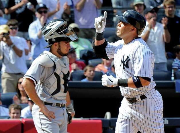 New York Yankees' Carlos Beltran, right, reacts as he comes home after hitting a home run while Chicago White Sox catcher Adrian Nieto, left, looks on during the sixth inning of a baseball game Saturday, Aug. 23, 2014, at Yankee Stadium in New York. The Yankees won 5-3. (AP Photo/Bill Kostroun) ORG XMIT: NYY113 Photo: Bill Kostroun / FR51951 AP