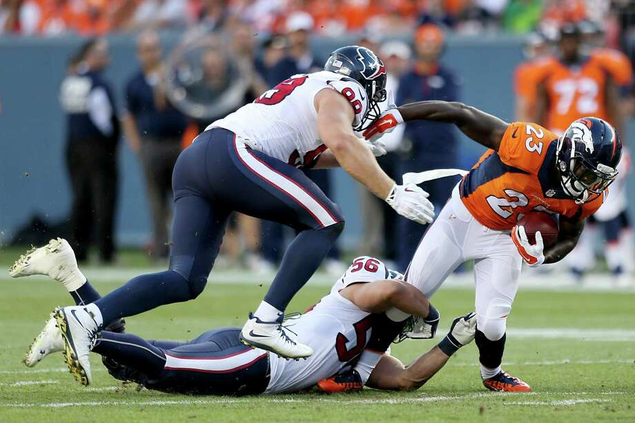 Broncos running back Ronnie Hillman, right, is brought down by Texans linebacker Brian Cushing (56) and defensive end J.J. Watt on Saturday night. Photo: Brett Coomer, Staff / © 2014  Houston Chronicle
