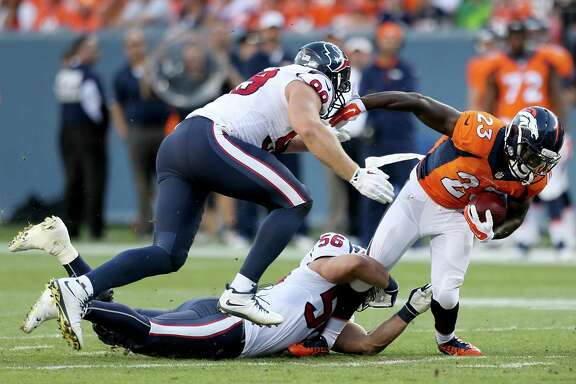 Broncos running back Ronnie Hillman, right, is brought down by Texans linebacker Brian Cushing (56) and defensive end J.J. Watt on Saturday night.