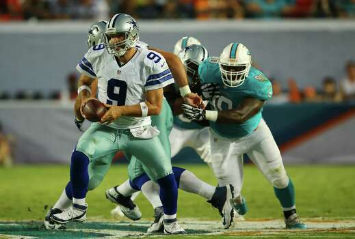 Cowboys QB Tony Romo (left), running with the ball, went 10 of 18 for 87 yards but was sacked three times in Saturday's 25-20 preseason loss at Miami. Photo: J. Pat Carter / Associated Press / AP