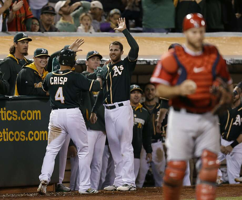 Coco Crisp gets a warm welcome after he scored the go-ahead run on a wild pitch in the eighth. Photo: Ben Margot, Associated Press
