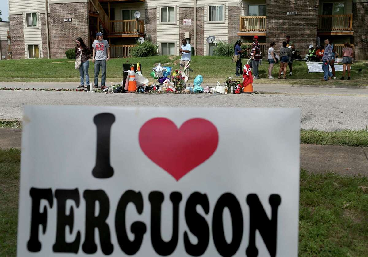 FERGUSON, MO - AUGUST 22: A sign is seen near the memorial setup on the spot where Michael Brown's body lay after he was shot by police on August 22, 2014 in Ferguson, Missouri. Protesters have been vocal asking for justice in the shooting death of Michael Brown by a Ferguson police officer on August 9th.