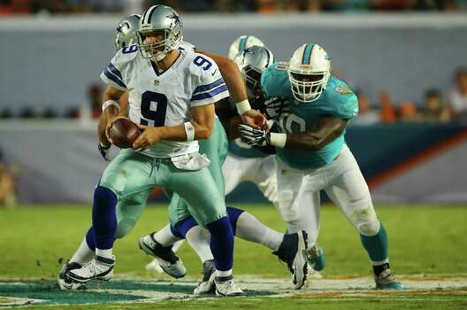 Cowboys QB Tony Romo (left), running with the ball, went 10 of 18 for 87 yards but was sacked three times in Saturday's 25-20 preseason loss at Miami, dropping Dallas to 0-3. Photo: J. Pat Carter / Associated Press / AP