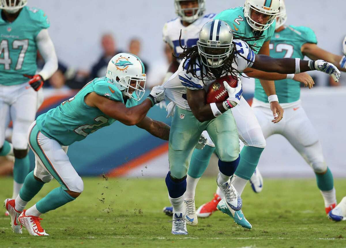 Miami Dolphins cornerback Cortland Finnegan (24) pulls the shirt of Dallas Cowboys wide receiver Dwayne Harris (17) during the first half of an NFL preseason football game, Saturday, Aug. 23, 2014 in Miami Gardens, Fla. (AP Photo/J Pat Carter)