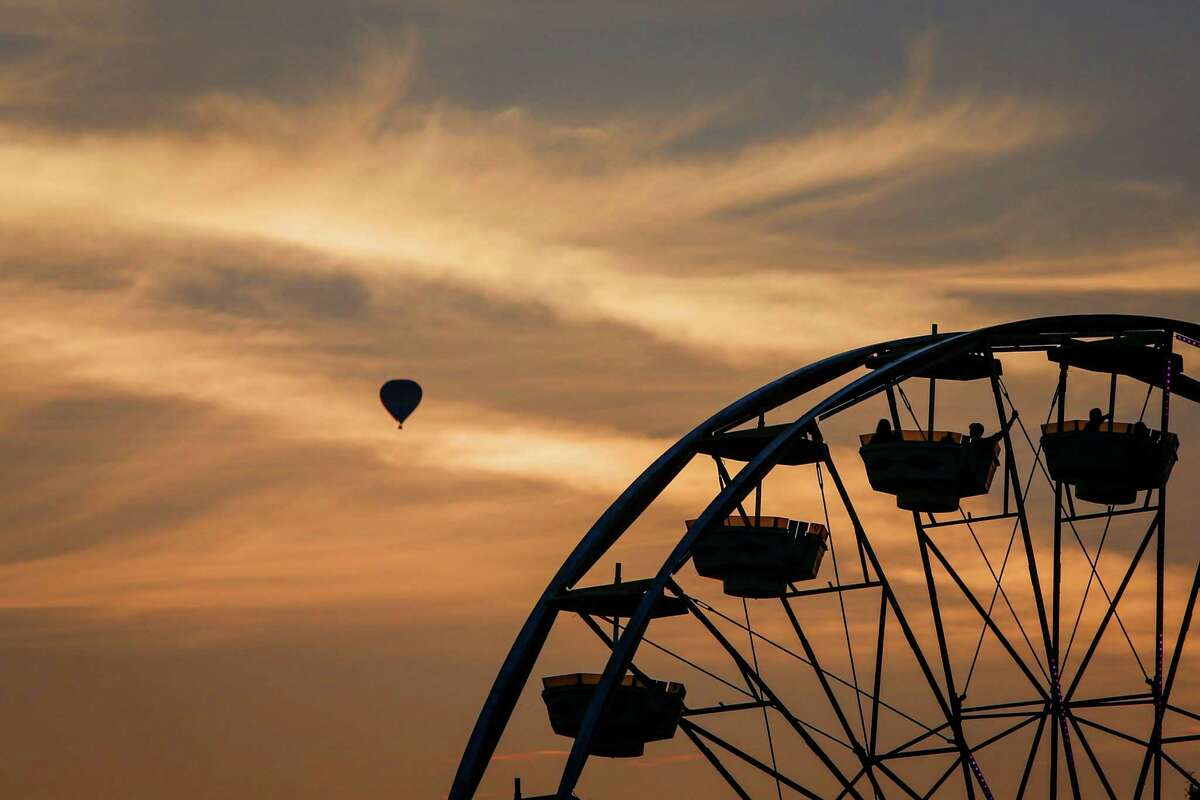 A ride is shown as a hot air balloon glides overhead during the first weekend of the Evergreen State Fair in Monroe. The annual fair continues through September 1. Photographed on Saturday, August 23, 2014.