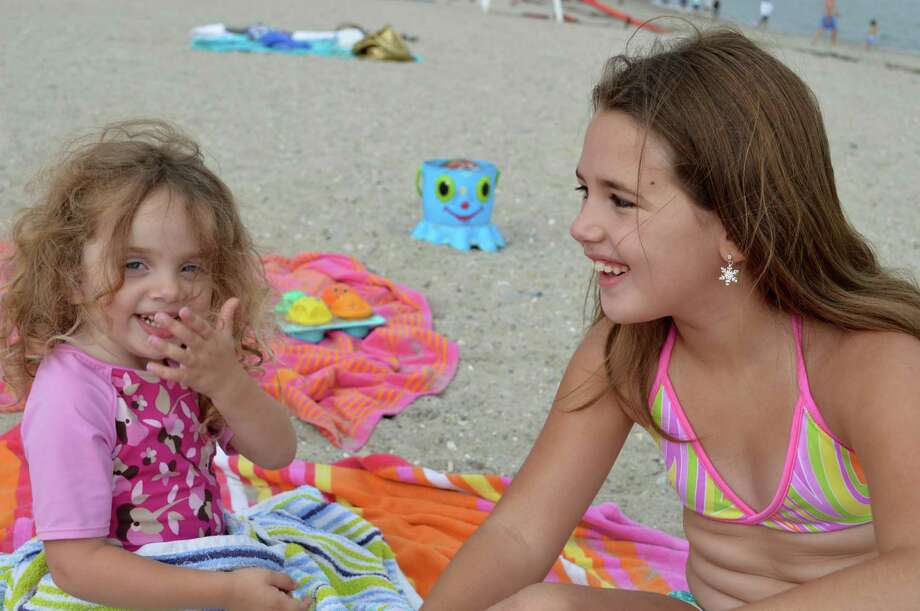 Sloane Bonvicino, 3, of Bellerose, N.Y., left, and Ava Pizzano, 7, of Weston, enjoy a moment at Compo Beach on Saturday. Photo: Jarret Liotta / Westport News