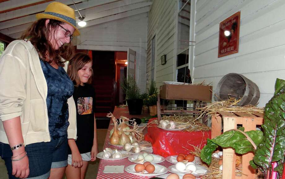 Fairfielders Sarah Frasco and Elise Wakeman check displays of eggs and produce at the Greenfield Hill Grange Agricultural Fair on Saturday. Wakeman is a descendant of the local Wakeman farm family and founders of the grange. Photo: Mike Lauterborn / Fairfield Citizen
