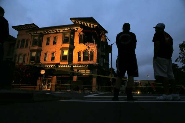 People look at earthquake damage to a building on Second Street in Napa, Calif. on Sunday, August 24, 2014, Photo: Scott Strazzante, The Chronicle