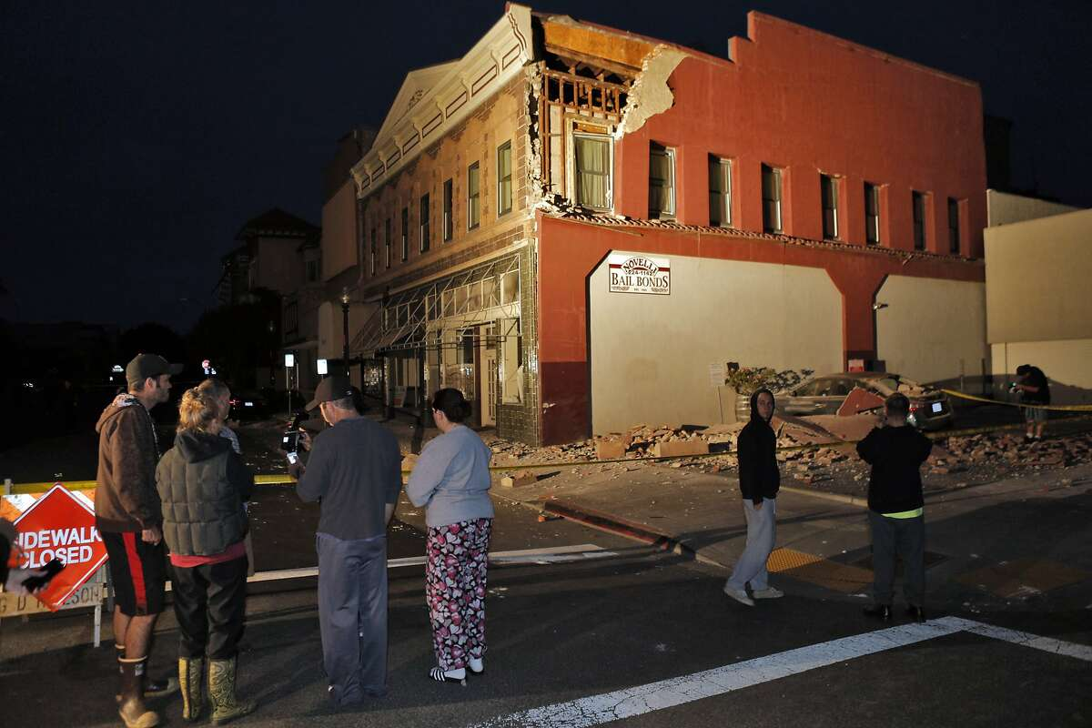 Residents of Napa check out damage to a building at Third and Brown Streets in Napa, Calif., after a strong earthquake hit the San Francisco Bay Area centered near American Canyon on Sunday, August 24, 2014.
