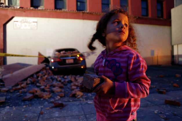McKenzie Edwards, 4, holds a souvenir brick that fell from Novelli Bail Bonds after an earthquake in Napa, Calif., on Sunday, August 24, 2014, Photo: Scott Strazzante / The Chronicle / ONLINE_YES