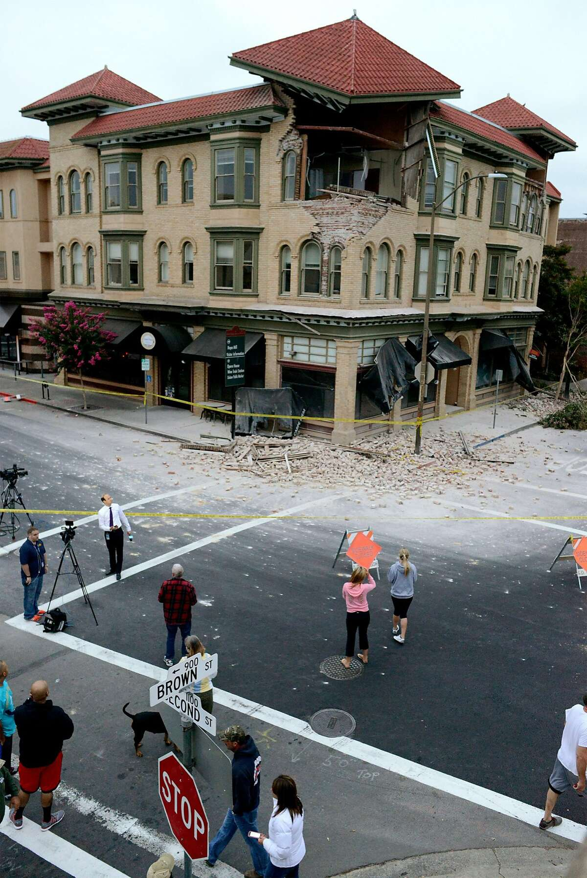 Spectators survey the damage to a building at the corner of Brown Street and Second Street in Napa, California, after an earthquake measuring 6.0 on the Richter scale struck in the early morning of August 24, 2014.