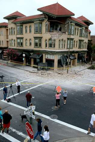 Spectators survey the damage to a building at the corner of Brown Street and Second Street in Napa, California, after an earthquake measuring struck in the early morning of August 24, 2014. Photo: Alvin Jornada, Special To The Chronicle