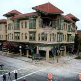 Spectators survey the damage to a building at the corner of Brown Street and Second Street in Napa, California, after an earthquake measuring struck in the early morning of August 24, 2014.
