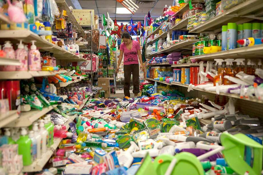 Nina Quidit cleans up the Dollar Plus and Party Supplies Store in American Canyon Calif. after an earthquake on Sunday Aug. 24, 2014. Quidit and her husband were woken up in the early morning hours by the store's alarm company and immediately drove in to begin clean up. The 6.0-magnitude quake caused six significant fires, including at four mobile homes, Napa Division Fire Chief Darren Drake said. (AP Photo/Alex Washburn) Photo: Alex Washburn, Associated Press