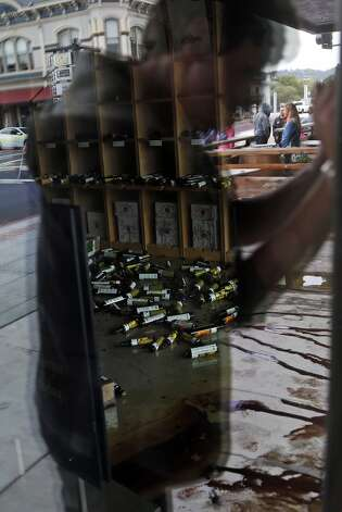 Mark Philpott photographs the broken bottles of olive oil strewn across the floor of Lucero Olive Oil after an earthquake in Napa, Calif. on Sunday, August 24, 2014, Photo: Scott Strazzante, The Chronicle