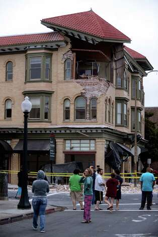 Spectators survey the damage to a building at the corner of Brown Street and Second Street in Napa, California, after an earthquake measuring 6.0 on the Richter scale struck in the early morning of August 24, 2014. Photo: Alvin Jornada / Special To The Chronicle / ONLINE_YES