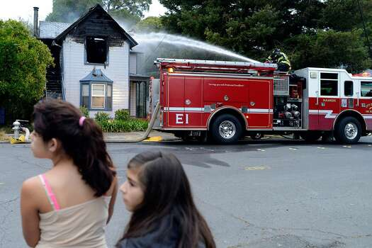 Karina Mendez, left, age 13, and Natasha Tomson, age 12, look around as they watch a City of Napa Fire Department engine company spray water on a home caught on fire after an earthquake measuring 6.0 on the Richter scale struck in the early morning in Napa, California,  on August 24, 2014. Photo: Alvin Jornada, Special To The Chronicle