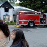 Karina Mendez, left, age 13, and Natasha Tomson, age 12, look around as they watch a City of Napa Fire Department engine company spray water on a home caught on fire after an earthquake measuring 6.0 on the Richter scale struck in the early morning in Napa, California,  on August 24, 2014.