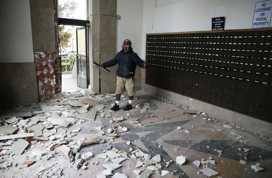 Jorge Sanchez looks over damage to the main post office following an earthquake Sunday, Aug. 24, 2014, in Napa, Calif. A large earthquake caused significant damage in California's northern Bay Area early Sunday, sending at least 70 people to a hospital, igniting fires, knocking out power to tens of thousands and sending residents running out of their homes in the darkness. (AP Photo/Eric Risberg) Photo: Eric Risberg, Associated Press