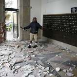 Jorge Sanchez looks over damage to the main post office following an earthquake Sunday, Aug. 24, 2014, in Napa, Calif. A large earthquake caused significant damage in California's northern Bay Area early Sunday, sending at least 70 people to a hospital, igniting fires, knocking out power to tens of thousands and sending residents running out of their homes in the darkness. (AP Photo/Eric Risberg)