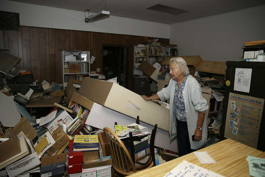 Jean Meehan looks over the damage to her JHM Stamp and Collectibles store following an earthquake Sunday, Aug. 24, 2014, in Napa, Calif. A large earthquake caused significant damage in California's northern Bay Area early Sunday, sending at least 70 people to a hospital, igniting fires, knocking out power to tens of thousands and sending residents running out of their homes in the darkness. (AP Photo/Eric Risberg) Photo: Eric Risberg, Associated Press